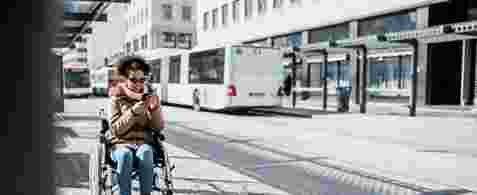 A woman using a smartphone in a wheelchair at a bus stop. A bus is in the background