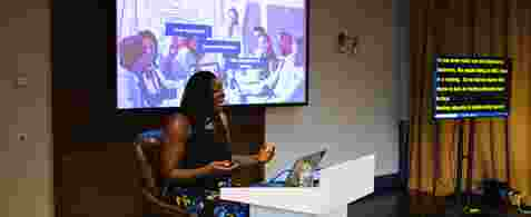 "Rachel Xavier. A black woman with mid length hair sat on a stool behind a podium. She is presenting with a large presenting screen displaying ""Meeting Etiquette"" behind her, and there's a subtitles screen to the right."