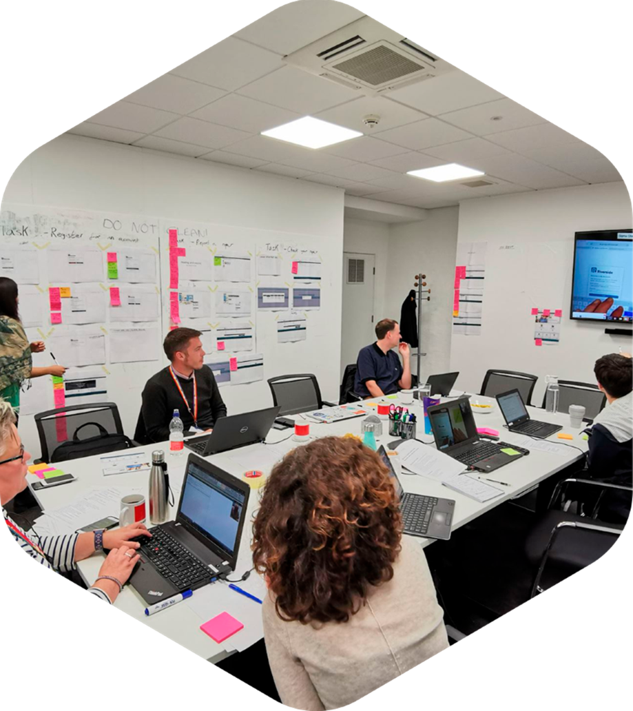 A white room with screenshot posters and post its stuck on the walls. Five people are sat around a white table. They are all looking at a large screen mounted on one of the walls.