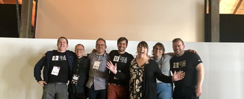 The Umbraco accessibilty team at the Codegarden 2019 conference. The group are white people stood in a line against a white wall. They are all smiling and happy.