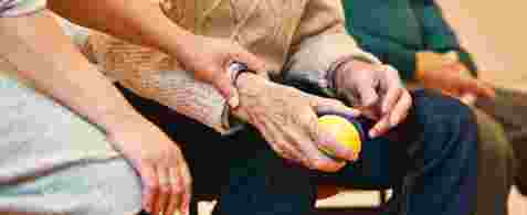 An elderly hand holding a ball. Another hand is resting on this hand with the ball.