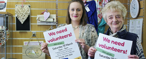 "Two white women volunteering in a charity shop, holding up posters reading ""We need volunteers"""