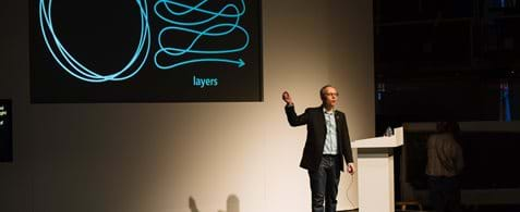 "Matt Edgar, a white man dressed in a casual suit and trainers, standing on stage with a presentation screen in the background. There's a squiggly line on the screen and with the word, ""Layers"" written below it."