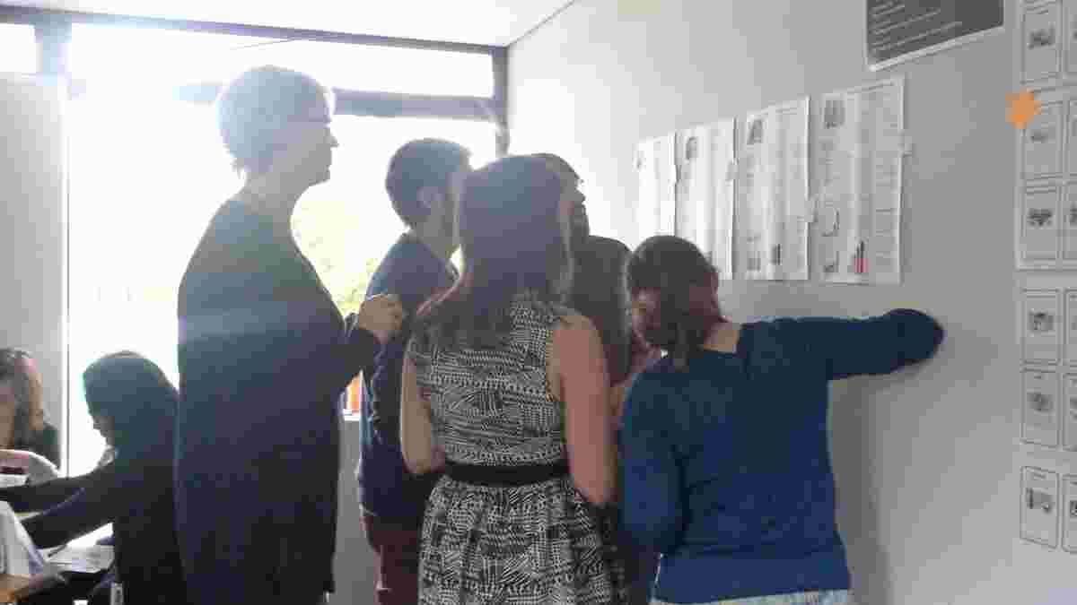five students looking at and discussing printed website pages on a wall in a design workshop