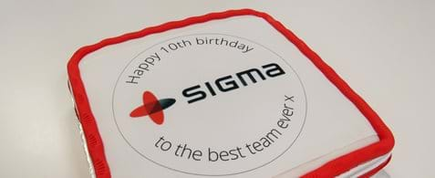 "A white cake with an iced red border with the Sigma logo on it and words reading, ""Happy 10th birthday to the best team ever x"""