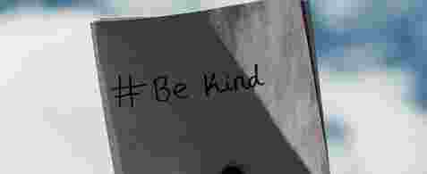 "A left hand holding a note with ""# Be Kind"" written on it up to the sky"