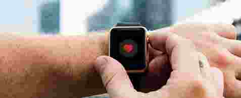 Arm with an apple watch on with a red heart displaying on the watch.