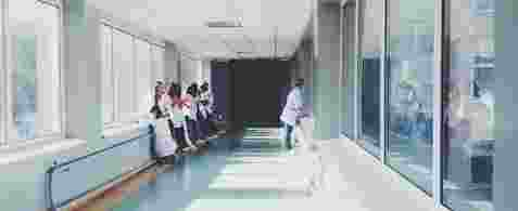 A long hallway with windows on both sides and Doctors And Patients stood against the side