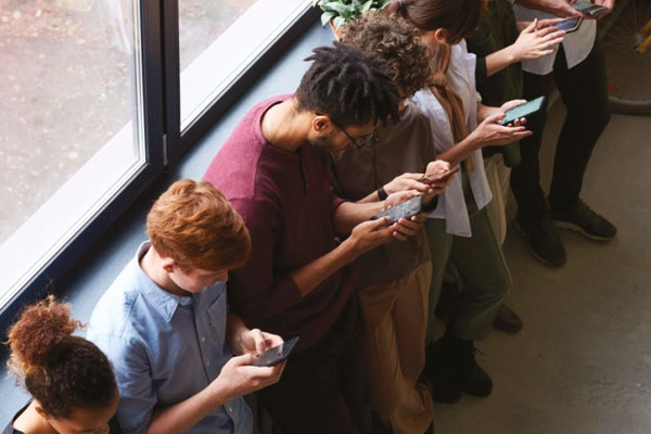 People stood against a wall all on their phones.