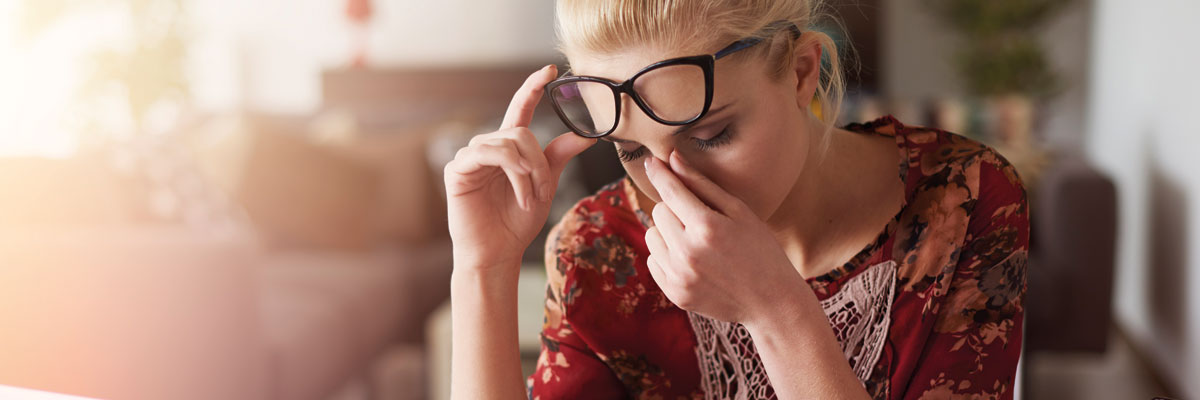 Woman with glasses on lifting them up her head whilst rubbing her eyes, looking stressed or tired